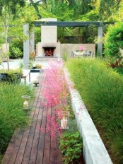 a wooden deck with candles and blooms that leads to a fireplace that creates a cozy and welcoming ambience