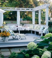 a small and cozy deck in white with a built-in bench and several loungers plus potted blooms and greenery