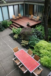 a small deck clad with rich stined wood and with wooden chairs that line it up