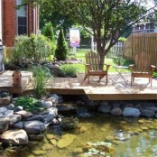 a rustic deck over the pond with rustic wooden furniture and rocks and blooms around
