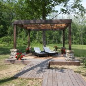 a rustic deck with wicker loungers, potted blooms and a view to the pond