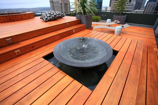 a minimalist deck done with orange wood, pillows, loungers, a fountain and potted greenery