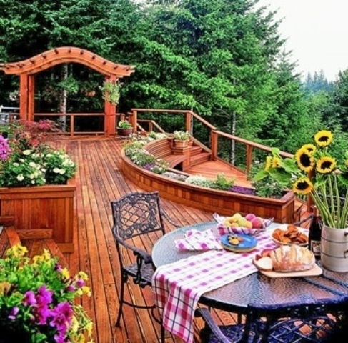a rustic wooden deck done with warm-stained furniture, with forged furniture and potted blooms