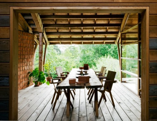 a rustic deck with a living edge table and wooden chairs and potted greenery for a fresh touch