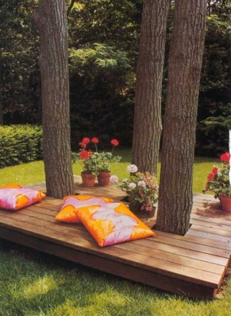 a contemporary deck with colorful pillows and potted blooms - the deck is integrated right into the trees