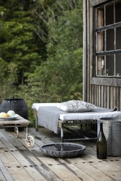 a Nordic deck with weathered wood on the floor and metal furniture – a bed, a chair, table and some buckets