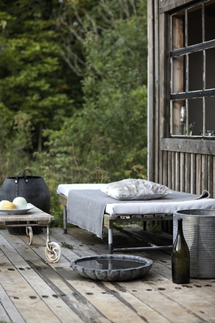a Nordic deck with weathered wood on the floor and metal furniture - a bed, a chair, table and some buckets