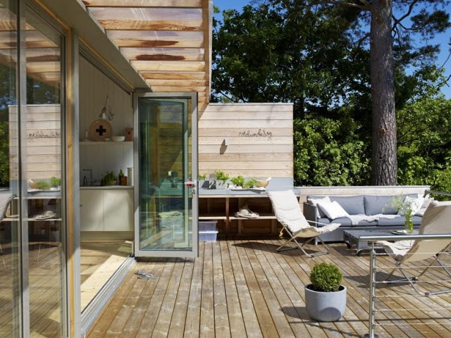 a contemporary deck with blue upholstered furniture, comfy sofas, loungers and potted greenery