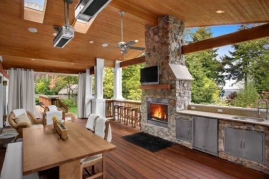 if your kitchen is located on a deck then combining it with lounge area with a fireplace is a super cozy way to go.