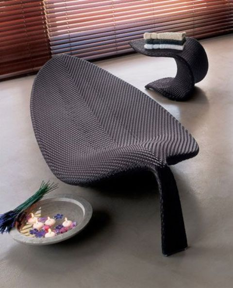 a dark wicker lounger shaped as a leaf is a unique and creative idea to finish off your outdoor space