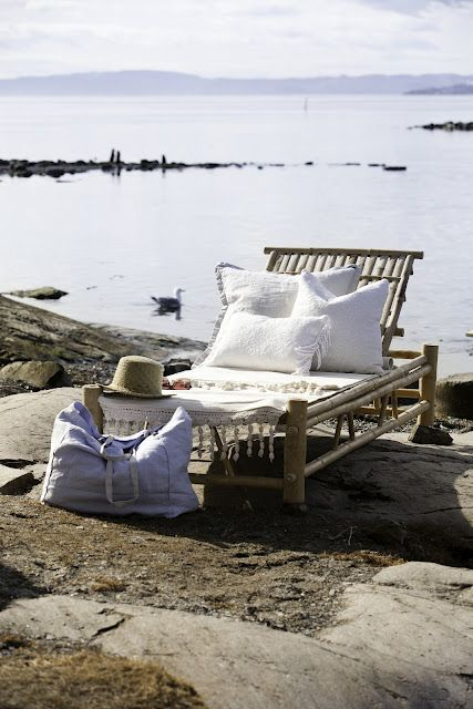 a tropical lounger made of neutral wood, with white upholstery and pillows and blankets looks dreamy and chic