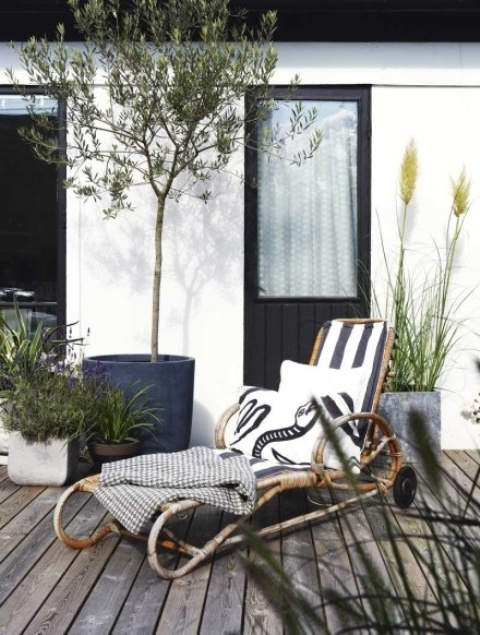 a rattan lounger with casters and elegant upholstery, pillows and blankets is a chic modern idea with a natural feel