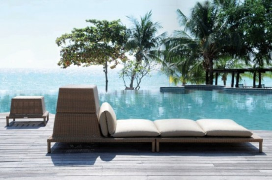 a large and long outdoor wicker lounger with some storage space is a cool idea to relax and to store towels in it