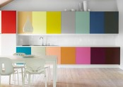 a minimalist rainbow kitchen with sleek cabinetry, a neutral dining set and a pendant lamp