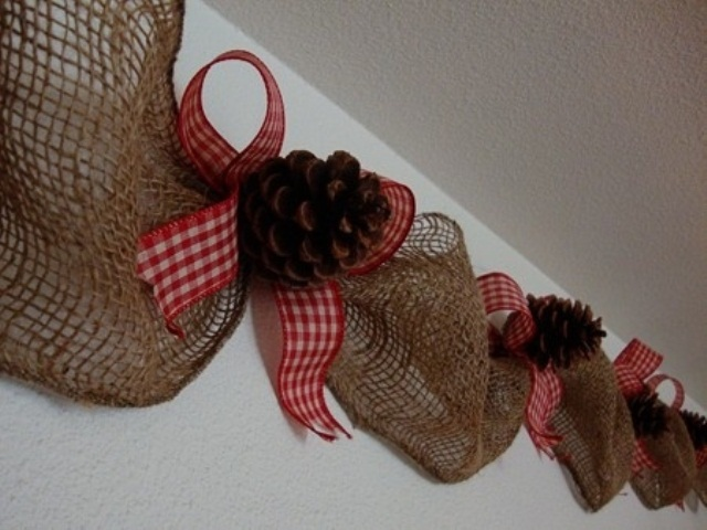 a burlap garland with pinecones and red plaid bows is a stylish Christmas idea with a rustic feel