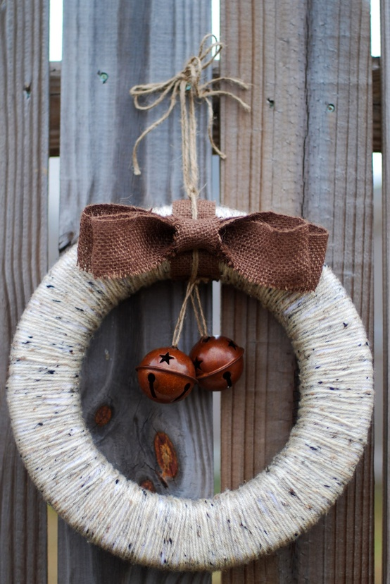 a yarn wrapped Christmas wreath with a brown bow and bells is a stylish rustic decoration