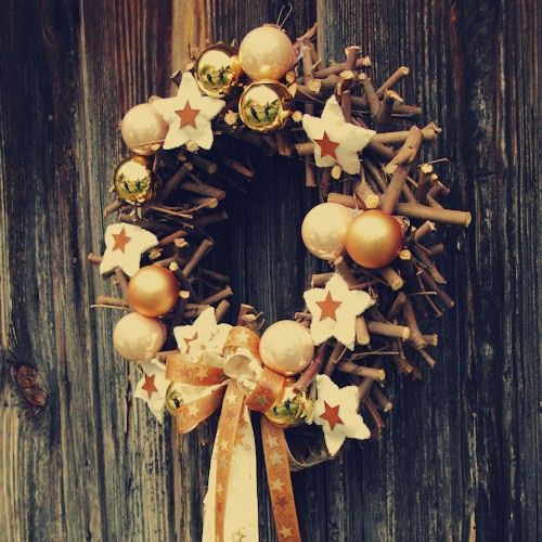 a rustic Christmas wreath of sticks, pretty metallic ornaments, stars and printed ribbons