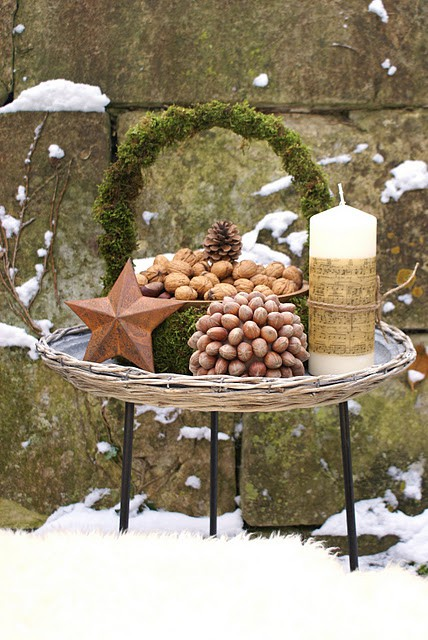 a rustic Christmas decoration of a moss wreath, a star, a large candle, nuts on a plate and a nut topiary