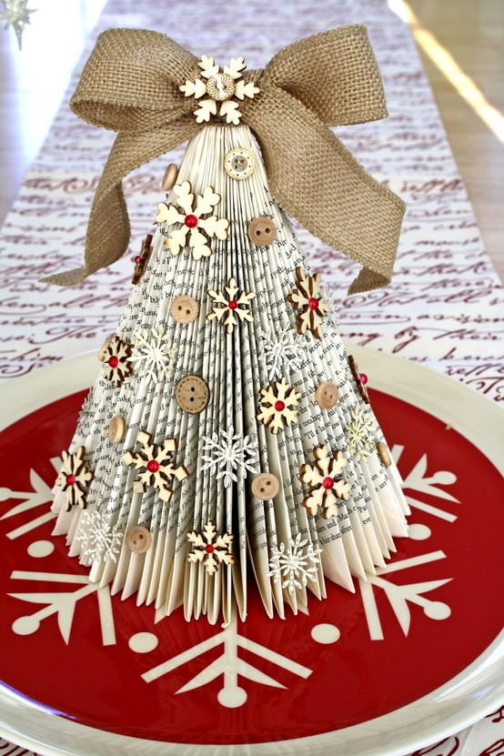 a rustic vintage Christmas tree of book pages, snowflakes and buttons and a large burlap bow on top