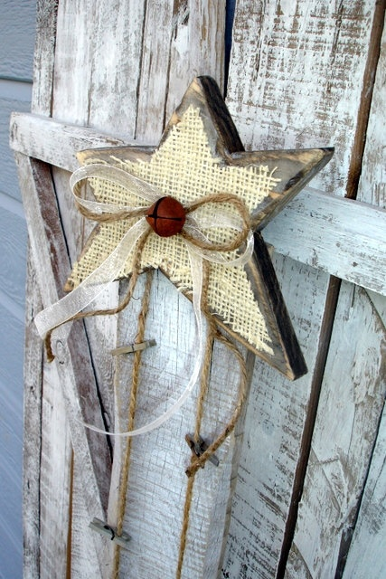 a wooden star Christmas decoration with burlap, a bell and a twine bow for a rustic feel