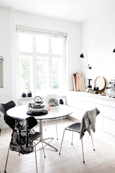 a small and airy Scandinavian dining nook with a round table and matching black chairs plus some vintage tableware is a very fresh solution