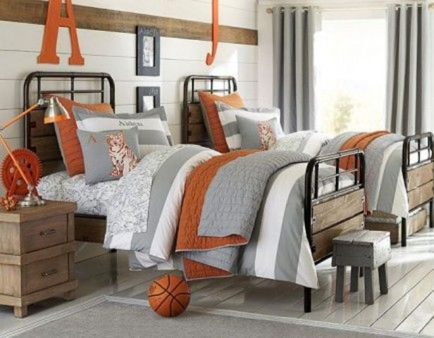 a rustic vintage shared teen boy bedroom with white walls, metal beds, wooden furniture and neutral and orange textiles