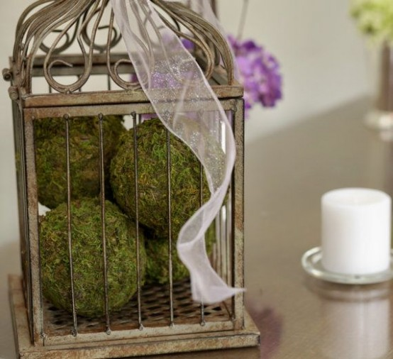 a cage with moss balls and ribbons on top looks very chic, vintage and elegant