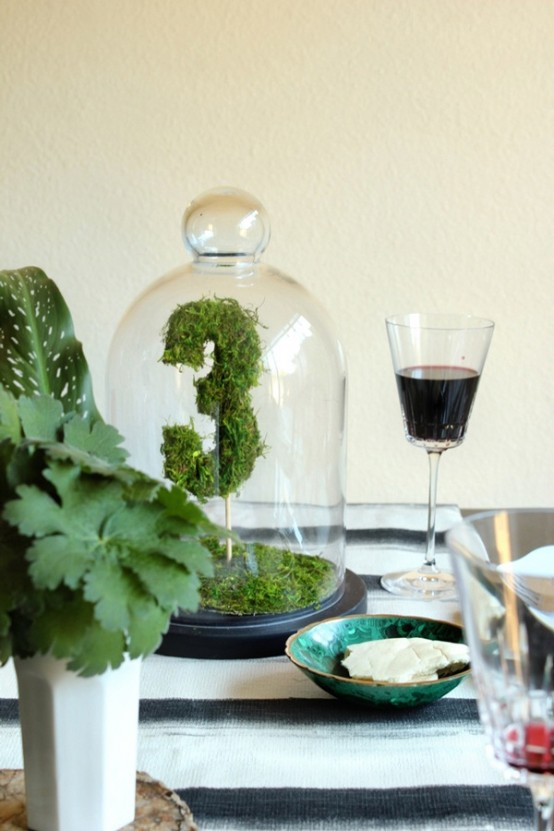 a moss table number on a stick placed in a cloche is a cool spring idea for special event decor