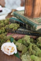a stylish centerpiece of fairy tale books, moss and blush blooms plus some candles on top