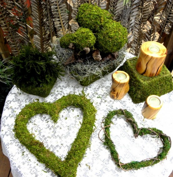 moss balls, moss hearts, a moss cube and candles in wooden candleholders for a springy feel