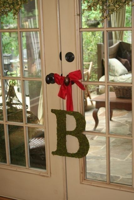a moss monogram with a red ribbon is a cool indoor or outdoor decoration for spring