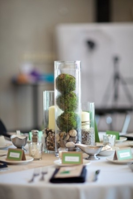 a simple centerpiece of a glass of pebbles and moss and some candles in glasses for a rustic feel