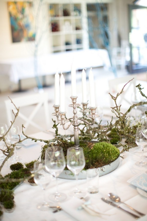 a spring centerpiece of a tin bowl, moss, branches and a chic vintage candelabra with candles