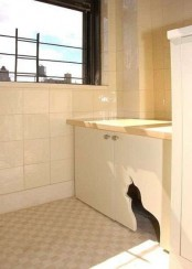 a neutral cabinet with a cat cutout for entrance and a cat litter box inside is a stylish and simple solution