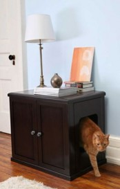 a dark stained cabinet with various items on top and a cat litter box inside is a cool idea for any space