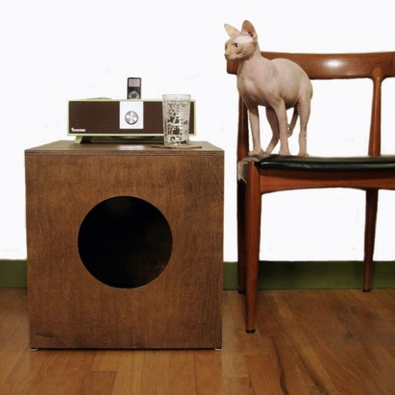 a dark stained box with a round entrance and a cat litter box inside is a stylish solution for a mid-century modern space