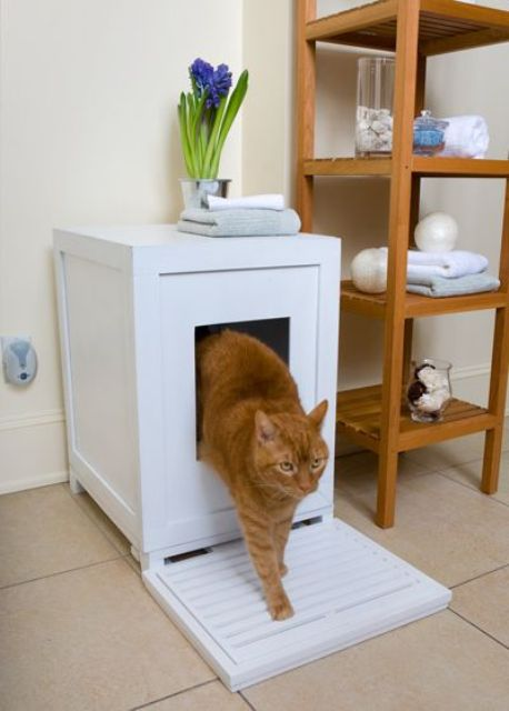 a small white box with a cat litter box and a wooden mat in front of it is a cool piece for a bathroom or powder room