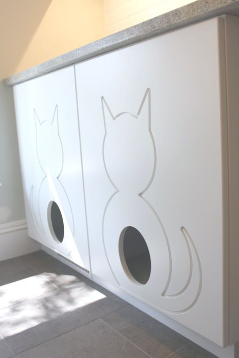 a large cabinet with a couple of litter boxes inside and two entrances for kitties is modern and simple