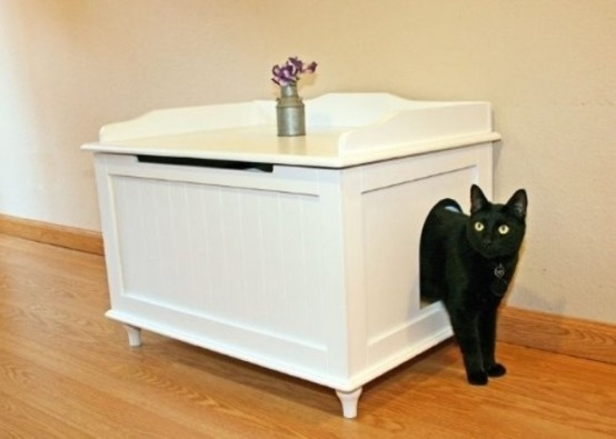 a small vintage bench with a storage space inside that can be used for storing a cat toilet there