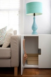 a white cabinet with a cat litter box inside and a shovel on the door is a simple and elegant solution