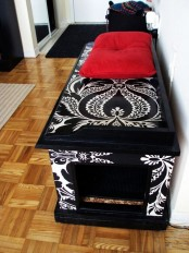 a stenciled black and white storage bench with a cat litter box inside and an entrance on one side