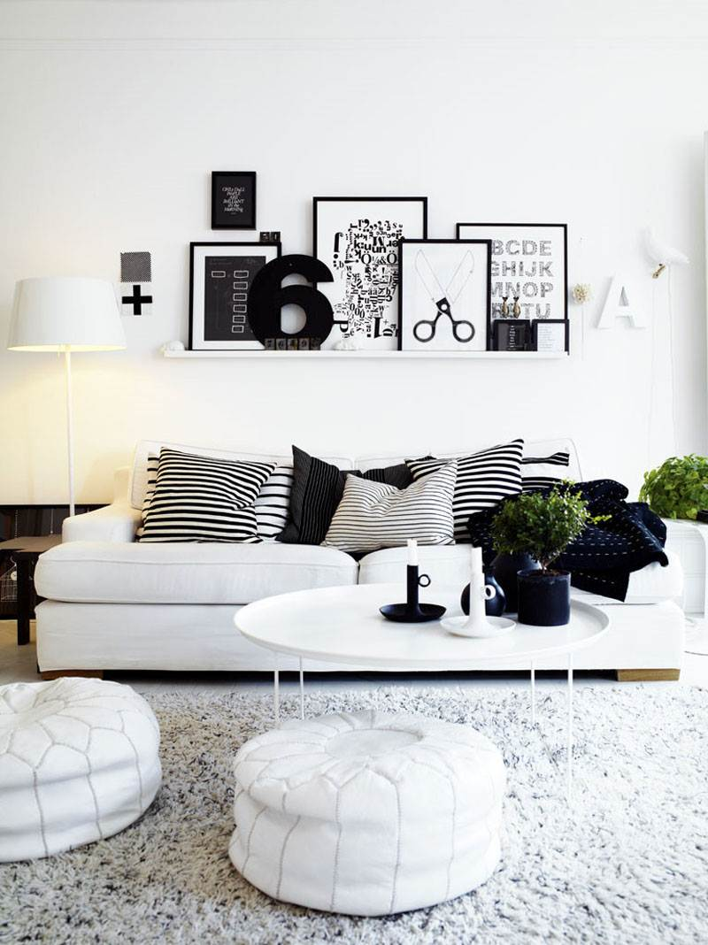 a Scandinavian living room done in black and white, with white furniture, black decor, greenery and a ledge with lots of artworks is very chic