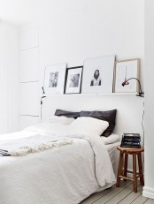 white ledges over the bed with pretty artworks are a great way to personalize your small bedroom without using any table or floor space