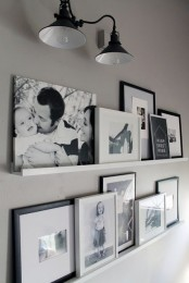 an elegant gallery wall done with white ledges and with black and white artworks in frames is a veyr stylish idea that will fit many spaces