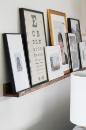 a wooden ledge with lots of artworks and photos is a lovely idea to create your own gallery wall with minimal effort