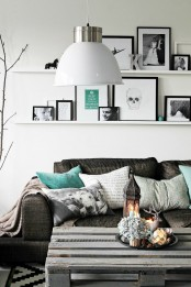 a monochromatic living room with dark and whitewashed furniture, ledges with black and white artworks and figurines and lanterns and pendant lamps