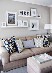 a modern neutral living room spruced up with bold pillows, with white ledges and various artworks is a very cool idea