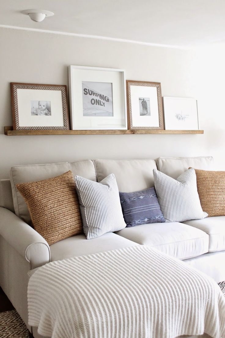 a neutral farmhouse living room done with a wooden ledge and artworks in wooden and woven frames is a very cozy and cool space