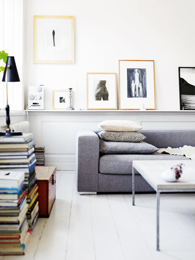a contemporary light filled living room with a long ledge and lots of artworks and candles that gives a cool art feel to the space