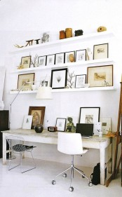a work space with ledges over the desk, with branches, artworks, vases, antlers and skulls for personalizing the space and making it bolder and cooler